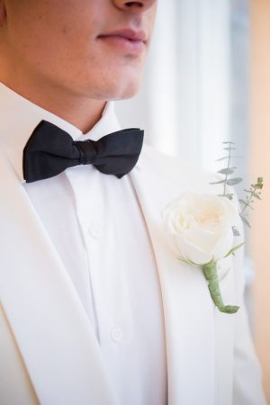 White groom tuxedo with black bow tie and white rose boutonnière - Elizabeth Nord Photography