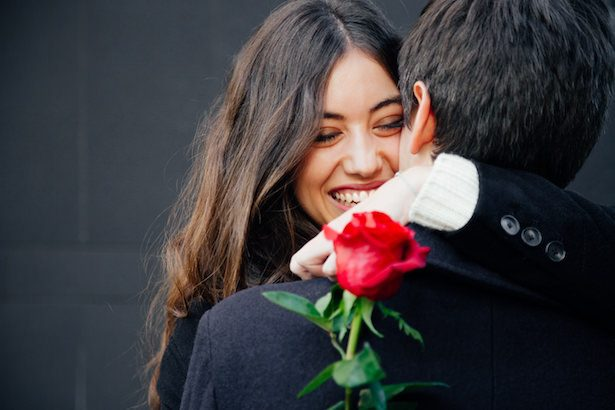 Wedding Proposal - Beautiful and happy young woman in love hugging her boyfriend holding a red rose
