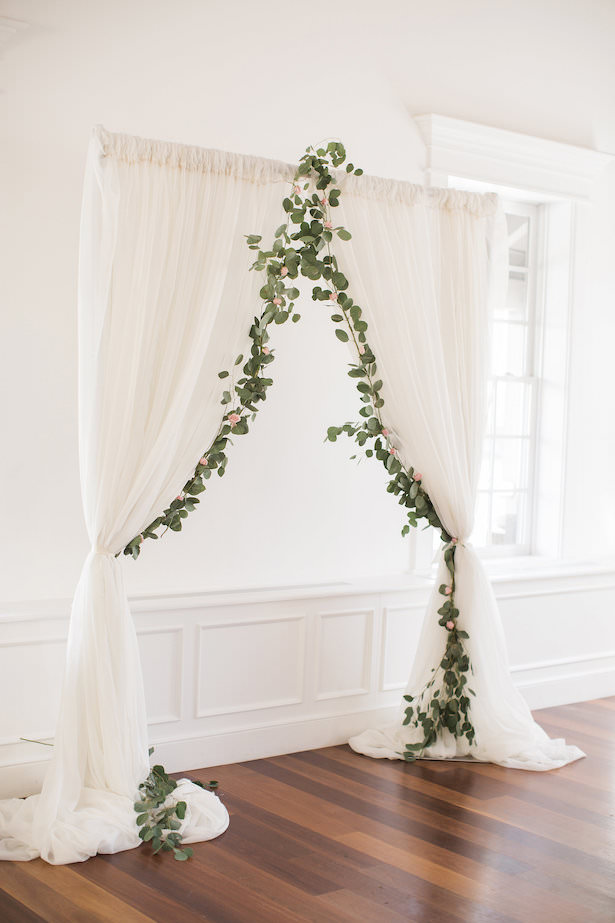 White wedding ceremony decor with greenery - Brooke Images