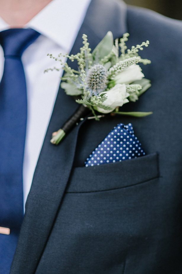 Groom on navy blue suit and white boutonniere- Nicole Jansma Photography