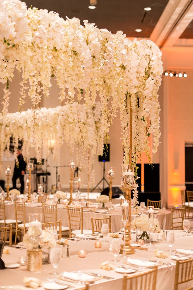 Hanging flower tall wedding centerpiece with white orchids and wisteria - Photographer: Julia Franzosa