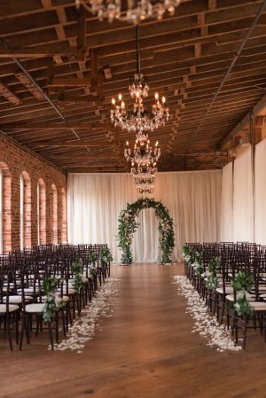 Indoor wedding ceremony decor with greenery arch - Photography by Marirosa