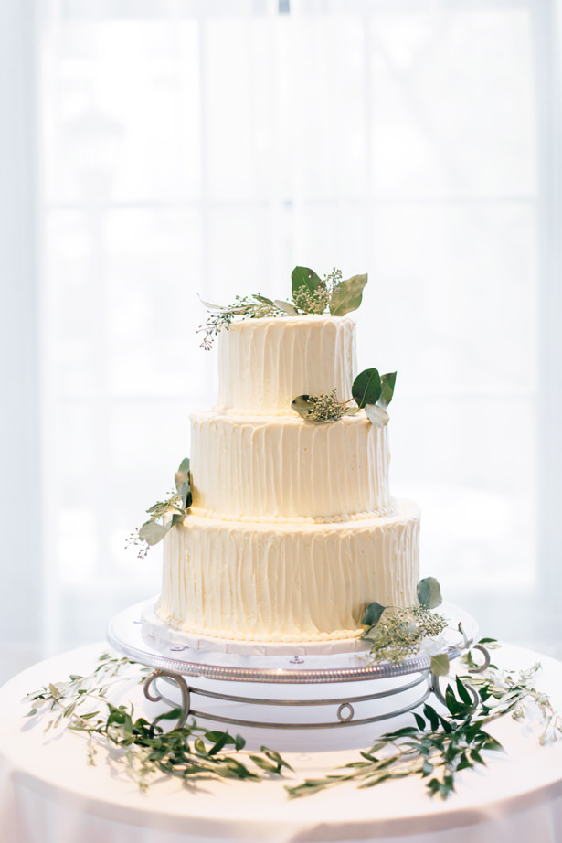 White buttercream wedding cake with greenery - Justina Louise Photography