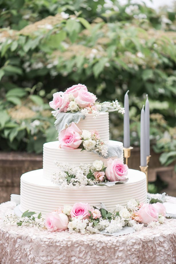 White buttercream wedding cake with fresh flowers and pink roses - Lynne Reznick Photography