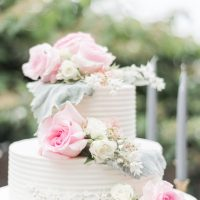 White buttercream wedding cake with fresh flowers and pink rosesLynne Reznick Photography