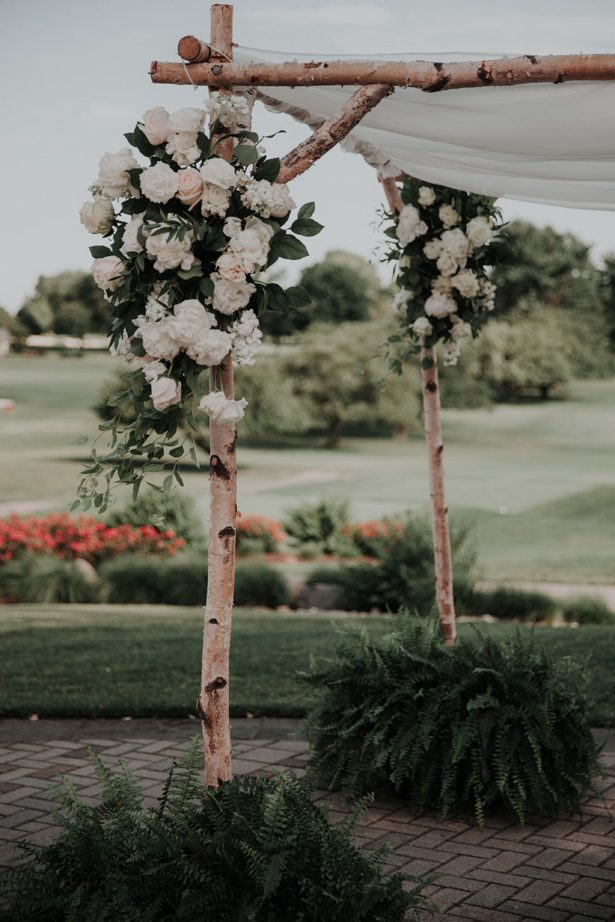 wedding flowers on wood wedding canopy - Kelli Wilke Photography