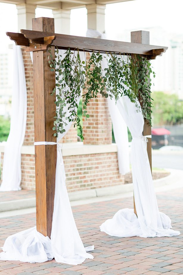 wood wedding arch with greenery - Luke & Ashley Photography