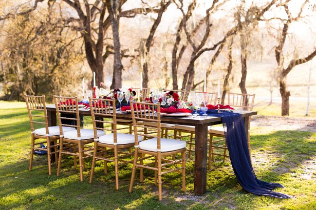 Burgundy and navy blue long wedding tablescape and gold chairs - Holley Elizabeth Photography