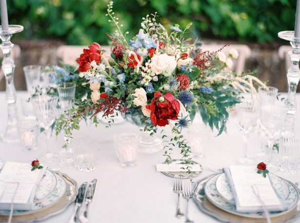 Low wedding centerpiece with red and blue flowers and greenery - Photography: The cablookfotolab