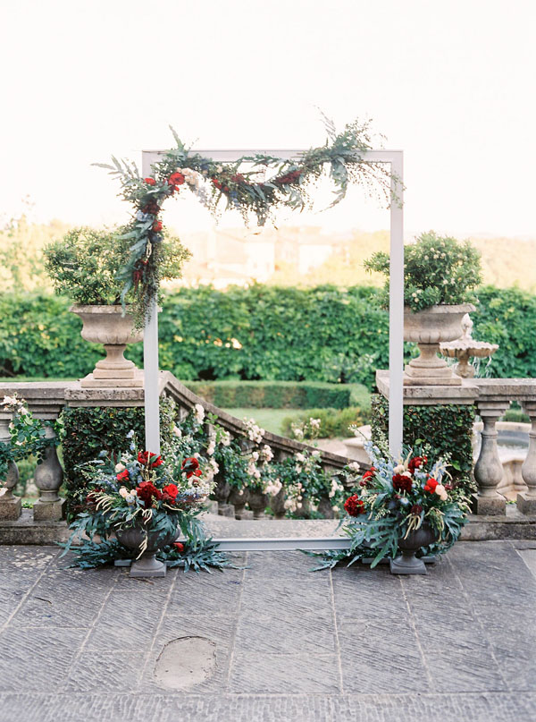 Outdoor arch wedding ceremony decor with red and blue flowers, and greenery - Photography: The cablookfotolab