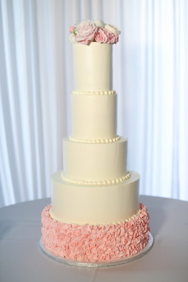 Tall white wedding cake with pink details and fresh flowers - Krystle Akin Photography