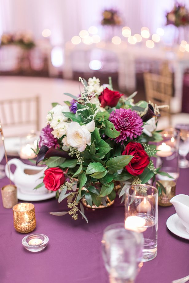 Low wedding centerpiece with colorful flowers on a purple linen - Photography: The Hendricks