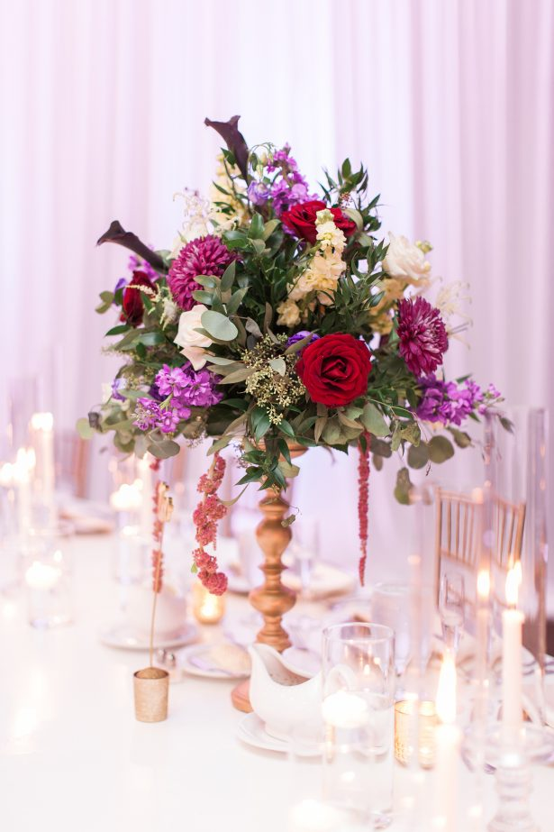 Tall wedding centerpiece with colorful flowers on gold vase - Photography: The Hendricks