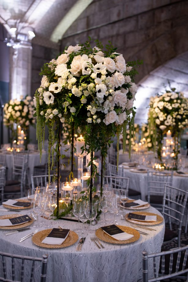 Tall wedding centerpiece with white flowers and greenery- Rafal Ostrowski Photography