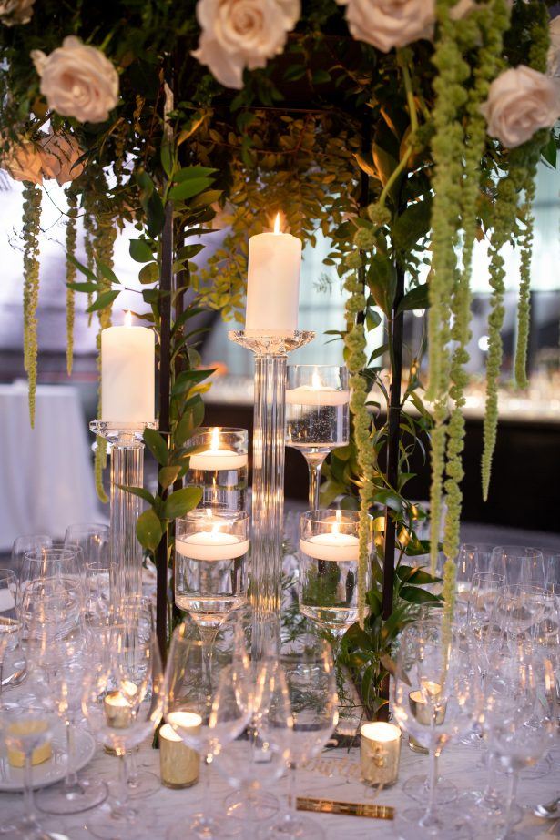 Tall wedding centerpiece with white flowers, candlelight and greenery - Rafal Ostrowski Photography