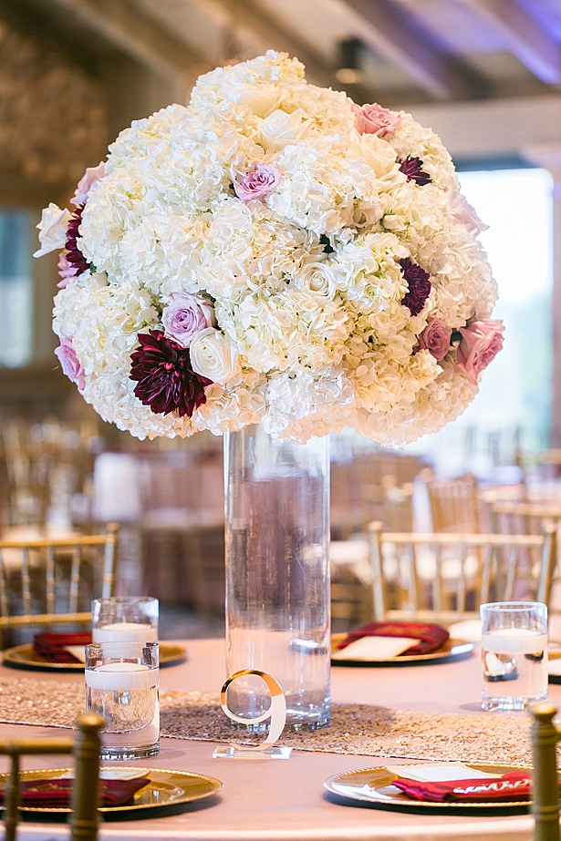 Flower centerpieces in white and burgundy for wedding reception A Glamorous Wedding with Fireworks - Rachael Hall Photography
