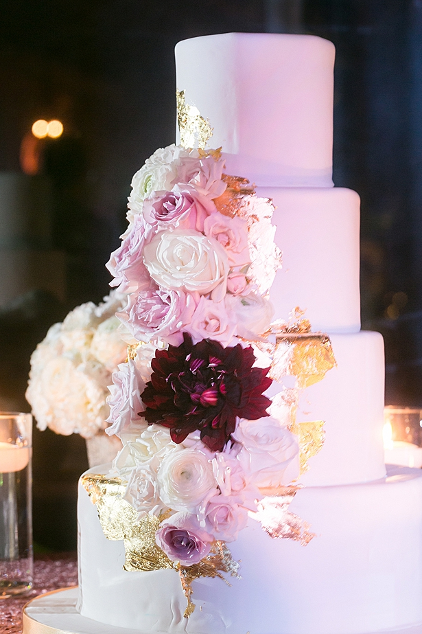 Glam white wedding cake with flowers A Glamorous Wedding with Fireworks - Rachael Hall Photography