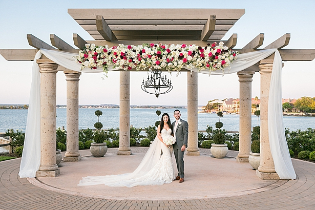 Luxurious lake wedding with flower pergola ceremony decor A Glamorous Wedding with Fireworks - Rachael Hall Photography