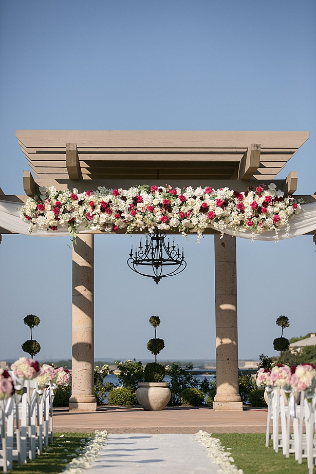 Stunning ceremony pergola with pink and white flowers A Glamorous Wedding with Fireworks - Rachael Hall Photography