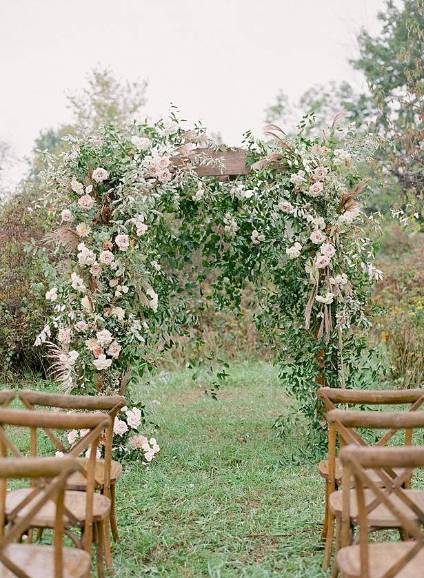 Whimsical ceremony arbor with blush and white flowers and greenery for outdoor ceremony Barn Wedding - Twah Photography