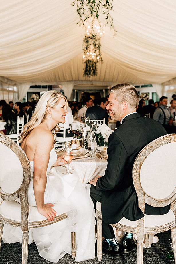 Bride and groom celebrating together at sweetheart table during reception - Jenna Bacholt Photography