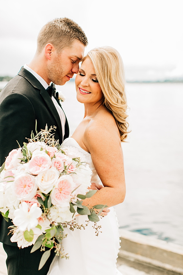 Classic photo of bride and groom on the water with white and pink bouquet - Jenna Bacholt Photography