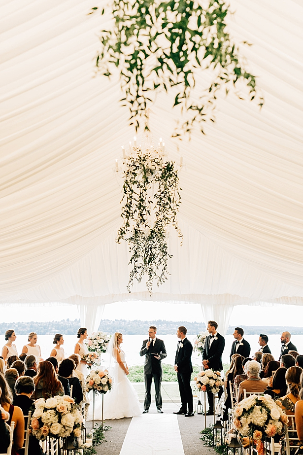 Elegant wedding ceremony by the water in a white tent with hanging chandeliers - Jenna Bacholt Photography
