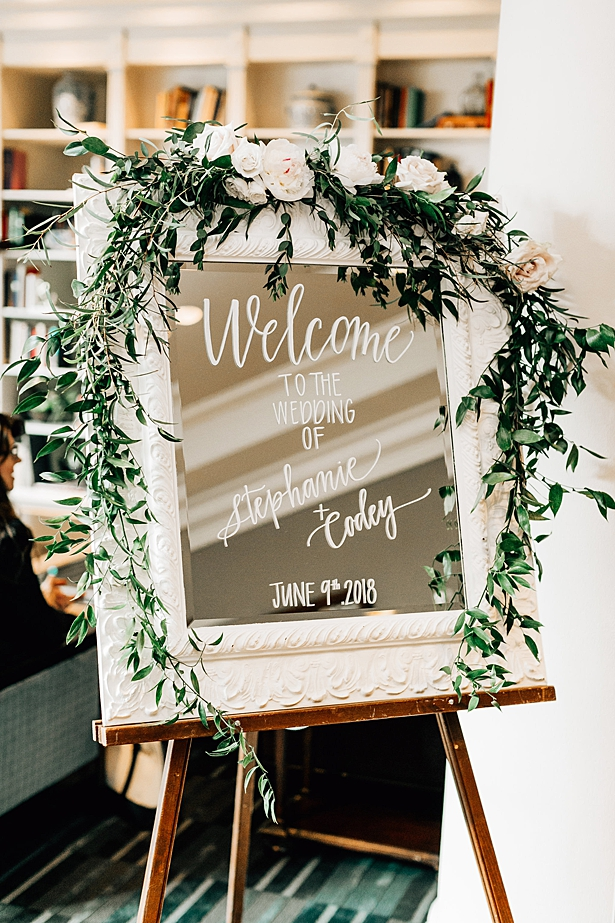 Wedding welcome sign with mirror and calligraphy in white frame with greenery and flowers - Jenna Bacholt Photography