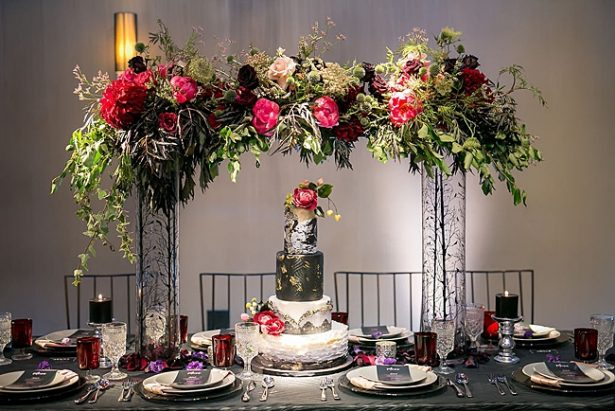 Bold and Glamorous wedding cake table with tall flowers and black and gold wedding cake - Little Honey Photography