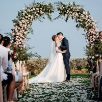 Bride and groom fist kiss under a floral wedding arbor - Madiow Photography