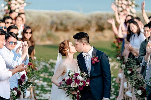Bride and groom kidding at the end of the aisle - Madiow Photography