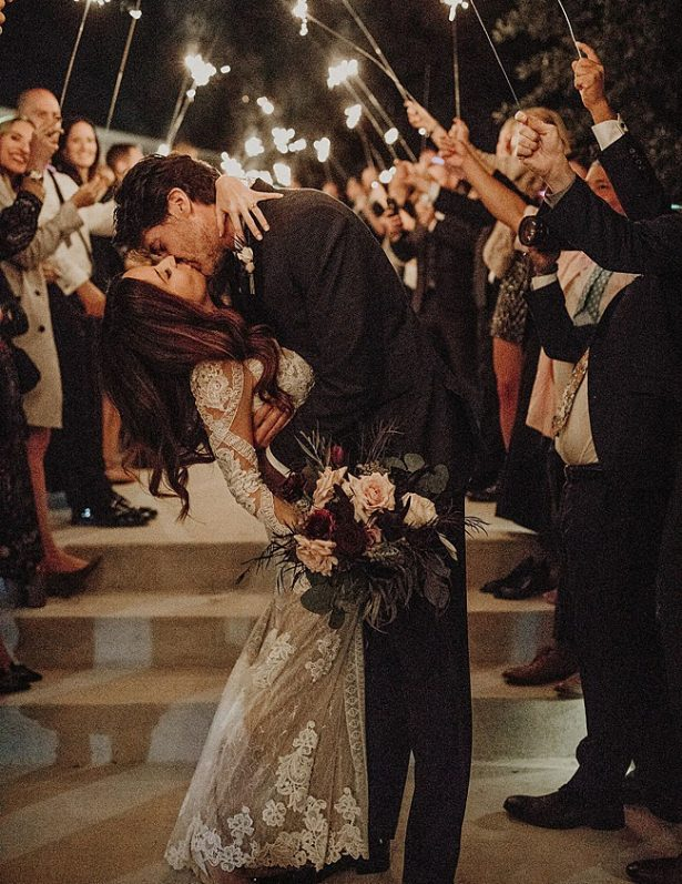 Bride and groom kissing during sparkler exit - Nikk Nguyen Photo