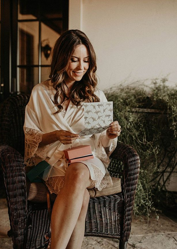 Bride reading letter from groom on wedding day - Nikk Nguyen Photo