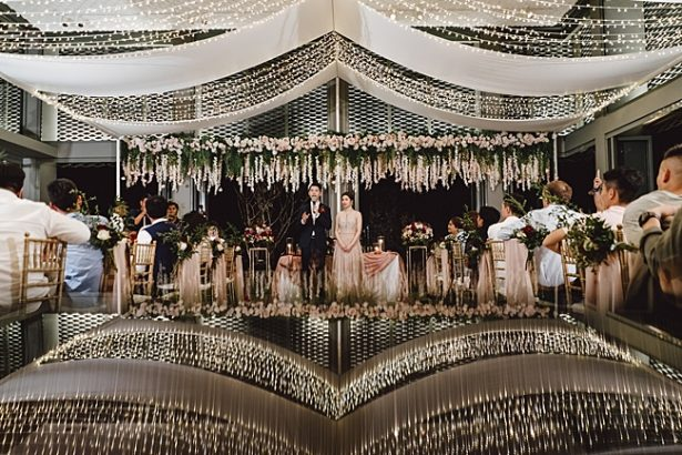 Epic hanging floral installation with string lights - Madiow Photography