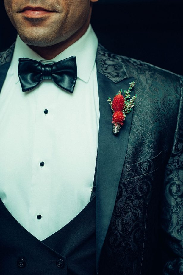 Patterned black suit jacket for groom with red boutonnière - Little Honey Photography