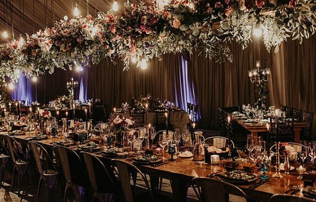 Romantic boho wedding reception decor with hanging flowers and candlesticks - Nikk Nguyen Photo