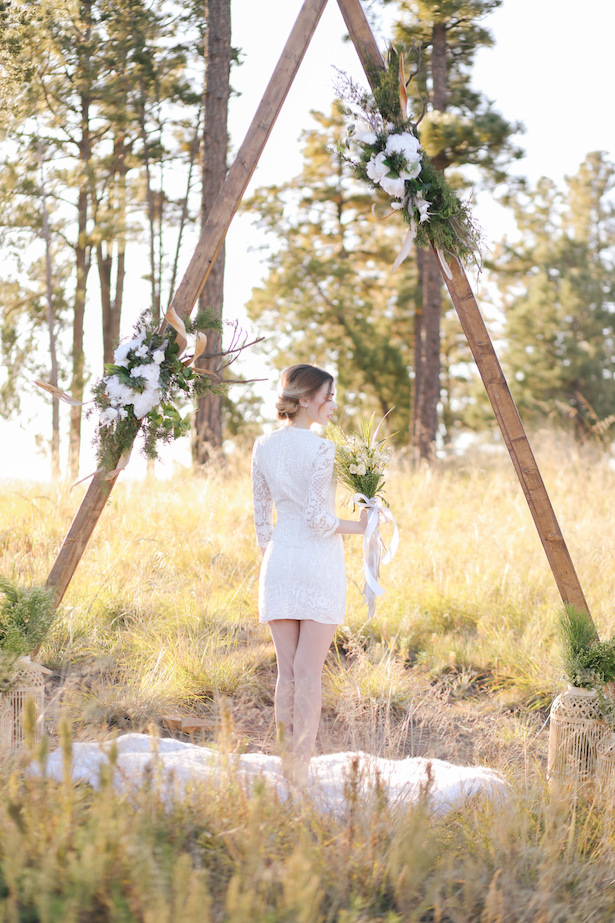 Boho wedding ceremony decor with bride in short lace wedding dress with sleeves - Photo: Tiffany Hudson Films
