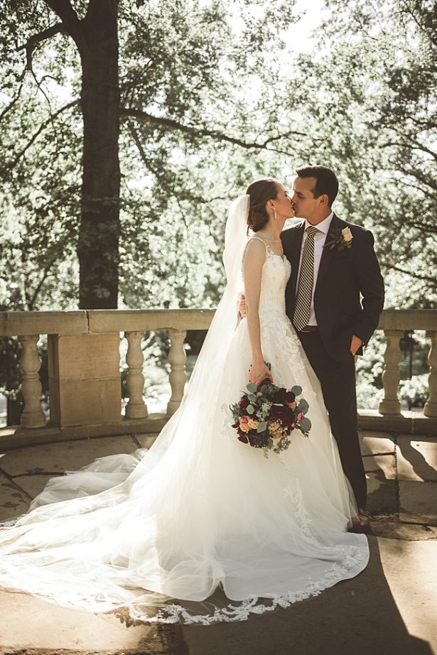 Bride and groom kissing with lace wedding dress and grey groom suit - Aileen Elizabeth Photography