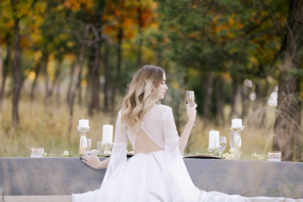 Bride at reception table with unique open back wedding dress - Photo: Tiffany Hudson Films