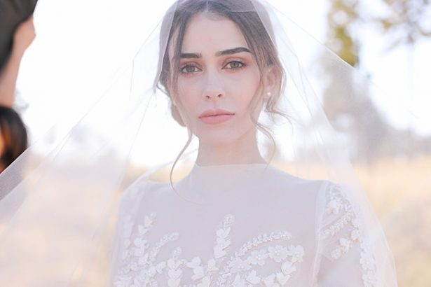 Classic bridal portrait of bride under her veil with updo - Photo: Tiffany Hudson Films