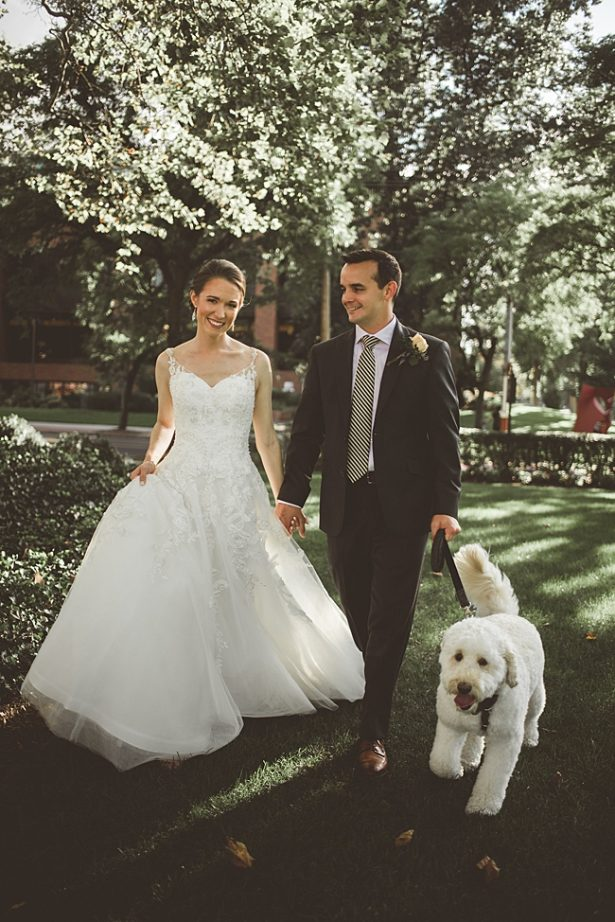 Elegant Fall Wedding photo of bride and groom walking with their goldendoodle dog ring bearer - Aileen Elizabeth Photography