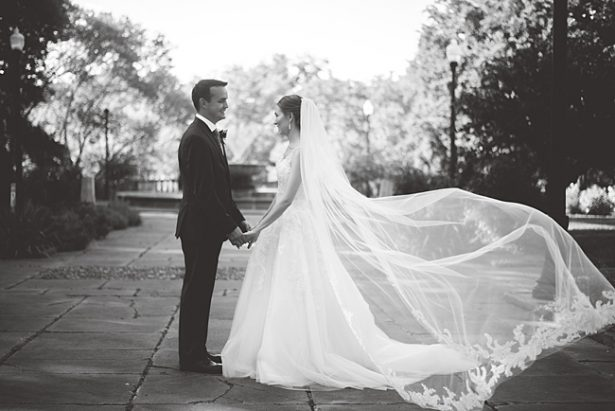 Romantic black and white photo of bride and groom holding hands with veil floating in the wind - Aileen Elizabeth Photography