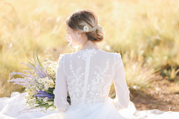Romantic long sleeve wedding dress with flowers and buttons up the back - Photo: Tiffany Hudson Films