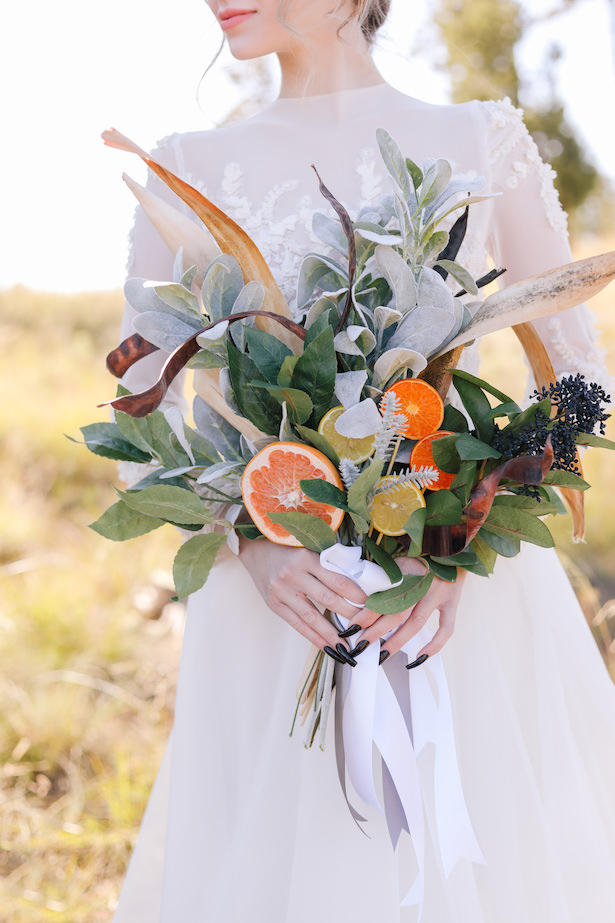 Citrus wedding bouquet and high neck lace wedding dress - Photo: Tiffany Hudson Films