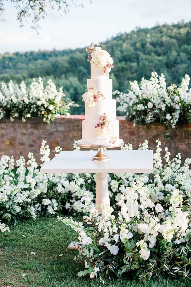 All white wedding cake and cake table surrounded by flowers- Purewhite Photography