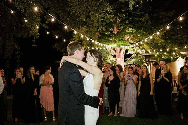 Bride and groom first dance under string lights in outdoor wedding reception - Purewhite Photography