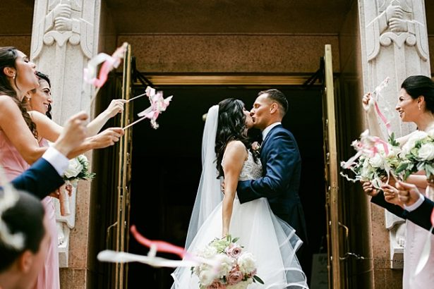 Bride and groom kissing during exit from ceremony with ribbon wands - Bluespark Photography