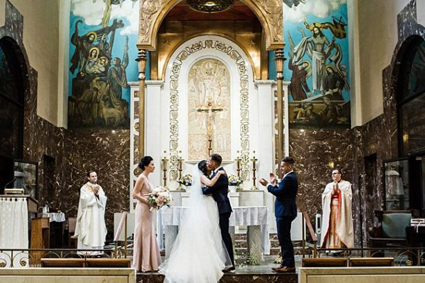 Cathedral wedding photo of bride and groom first kiss - Bluespark Photography