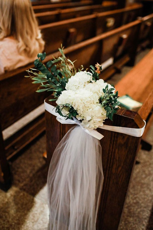 Church wedding flowers for pew with white flowers and tulle - Bluespark Photography