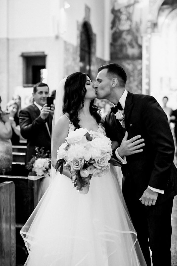 Church wedding recessional photo of bride and groom kissing - Bluespark Photography